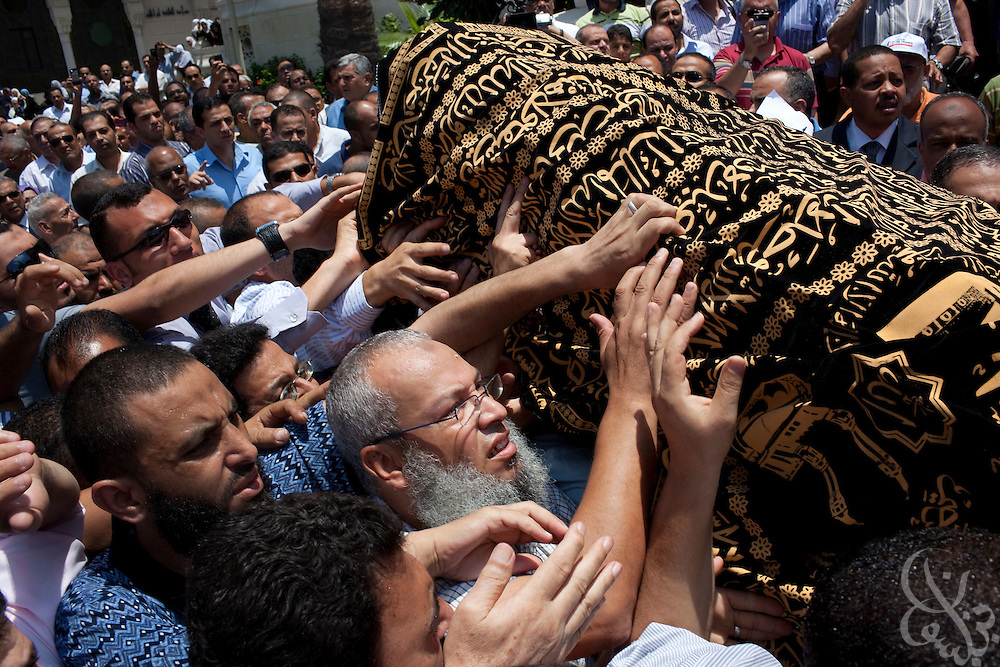 "Egyptians reach out to touch the casket of the ""headscarf martyr"" Marwa Sherbini, 31, at her funeral in the Egyptian port city of Alexandria July 6, 2009. Sherbini was stabbed to death inside a German courtroom by a 28 year old attacker, Axel W., who had been previously convicted of insulting her religion. Newspapers in Egypt have expressed outrage over the attack and have dubbed her the ""martyr of the hijab"" and ""headscarf martyr."""