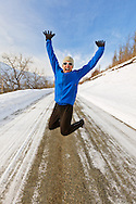 A male jogger jumps in exhilaration along Hiland Road in South Eagle River with the Chugach Mountains and Chugach State Park in the background in Southcentral Alaska. Winter. Afternoon. MR.