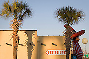 """A fiberglass statue of rest stop mascot """"Pedro"""" stands beside palmettos and restrooms at South of the Border near the N.C./S.C. state line on I-95."""