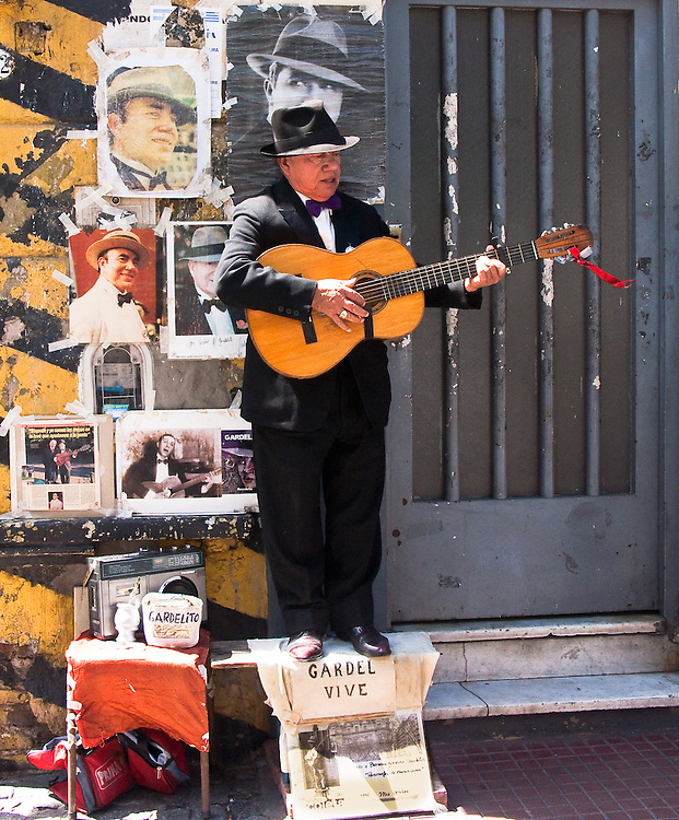 Standing on a bench on Calle Defensa with photos of Carlos Gardel behind him. Buenos Aires, Argentina.