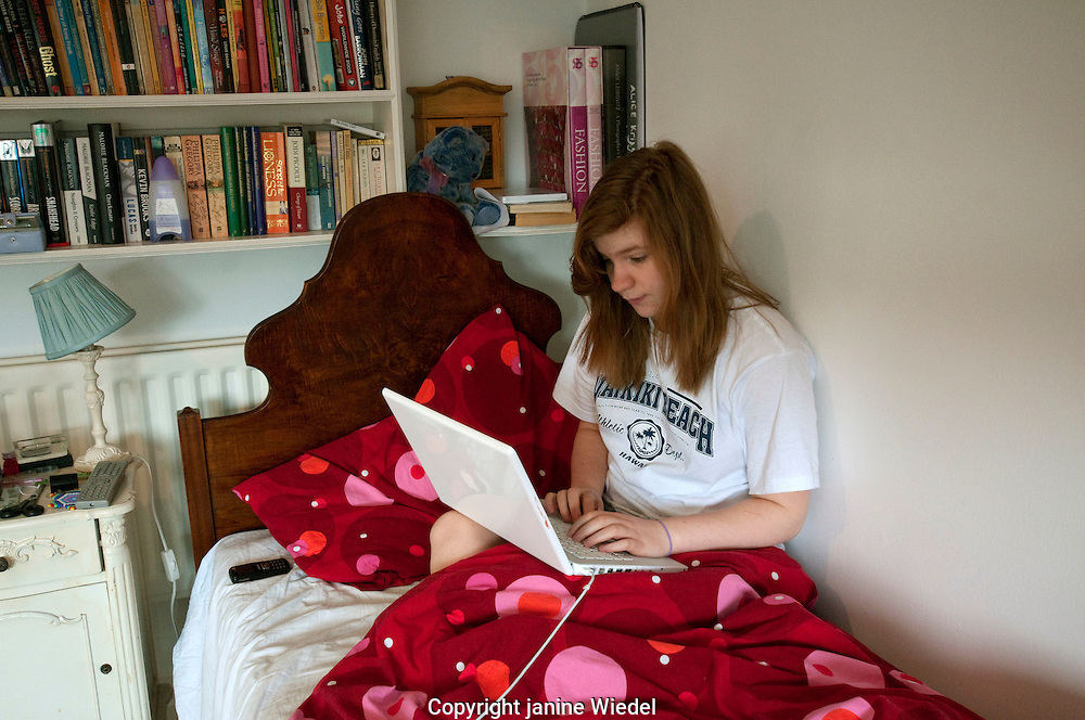 Teenaged girl sitting up in bed working on computer