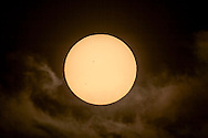 The May 9, 2016 transit of Mercury taken about 45 minutes after sunrise, as the Sun emerged from low horizon cloud. Taken from Kamloops, British Columbia, where the transit was well underway at sunrise. Mercury appears as the circular dot at lower left, with a sunpot group above centre. <br /> <br /> I shot this with the 130mm Astro-Physics refractor at f/6 prime focus with the Canon 60Da camera at ISO 100. Shot through a Kendrick white light solar filter.