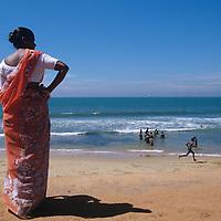 Sri Lanka, Woman walks on beach along beach by Galle Face Green