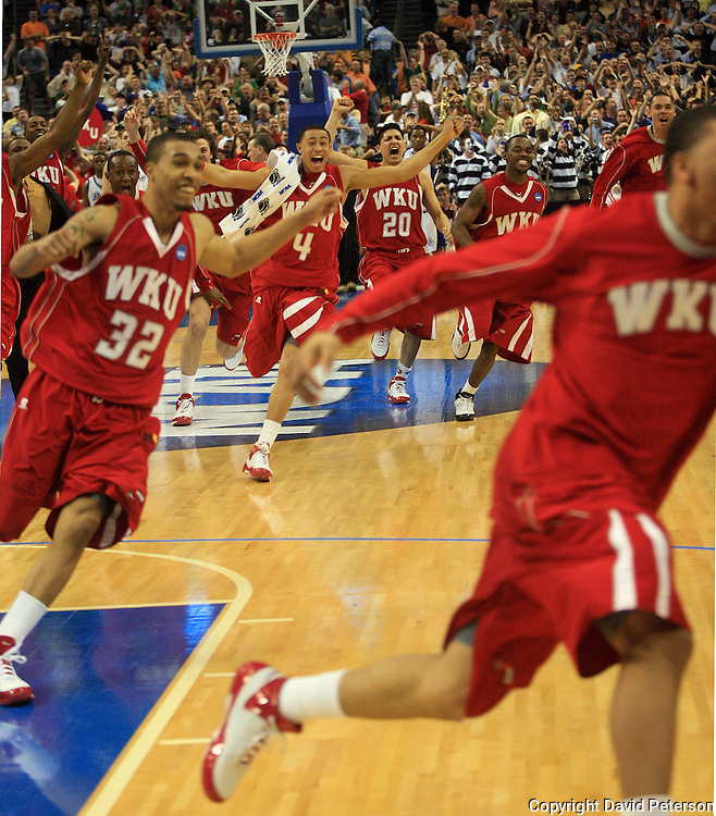 """Players from Western Kentucky University sprint onto the court at the St. Pete Times Forum Friday, after they stunned Drake University with a winning buzzer-beating 3 point shot in the NCAA Basketball Tournament Western Regional played in Tampa, Florida.  The shot, made by Ty Rogers was about 6 feet beyond the 3 point arc.  The win was another example of """"March Madness"""", where upsets by lower seeded teams are common.  Drake was a 5th seed and Western Kentucky was a 12th seed."""