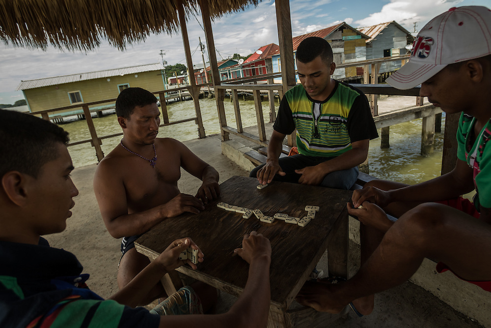 "CEUTA, VENEZUELA - AUGUST 28, 2014: Fishermen play dominoes after work in Ceuta, a community of ""palafitos"", shacks built on posts above Lake Maracaibo, where much of Venezuela's oil reserves are concentrated. Despite being so close to wells that have brought Venezuela tremendous oil wealth, residents of Ceuta live in impoverished conditions. PHOTO: Meridith Kohut for The New York Times"