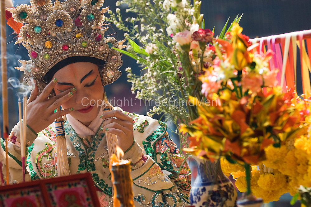 Chinese religious festival in a small town. Participant in costume at outdoor theater.<br /> Thailand.
