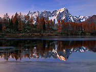 This is Arpy lake in Valle d'Aosta, Italy, with the peaks and glaciers of part of the Monte Bianco range in the background. Taken about 40 minutes after sunset on a cold evening of mid October, when the wind had calmed down and the water  was perfectly still.  The fact that the lake was already partially frozen provided some nice interest to the foreground, with the thin layer of floating ice.
