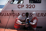 Italy: MSF Dignity1: A sick migrant rescued at sea is helped by Italian coastal guard officials to be transferred on the Dignity1 on August 23, 2015. Alessio Romenzi