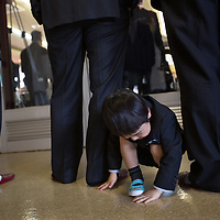 A young boy plays in amongst the legs of elder men, at the commencement of the School and kindergarten entrance ceremony, at Kawauchi community centre, in Kawauchi, Japan on Friday 6th April 2012. Restrictions on residents living in, and visiting their homes and business in Kawauchi, have just been relaxed and approximately 533 people have moved back out of an original town population of 2,856. The residents initially left due to fears over high levels of nuclear radiation contamination from the explosions at the Fukushima Daiichi nuclear plant which is approximately 25-30km away from the town. The nuclear plant exploded in the aftermath of the earthquake and tsunami which hit the Tohoku coastline on 11th March 2011.