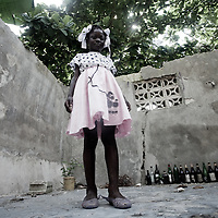 A girl stands in what used to be her house - destroyed in the January 12 2010 earthquake