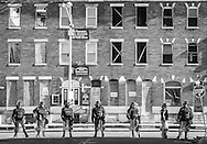Police officers secure a perimeter during riots in the streets of West Baltimore