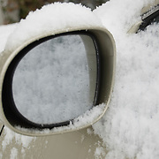 A side rear view mirror reflects snow covering a car after a winter snowstorm in South Carolina.