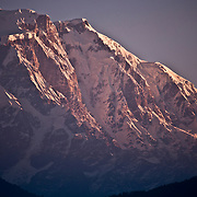 Photographed at sunrise, the impressive southwest face of Annapurna VI (7,525 meters) rises above the town of Pokhara in western Nepal.
