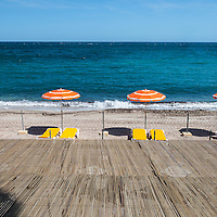Orange and white beach umbrellas along the coast in St. Jean Cap Ferrat in the South of France.