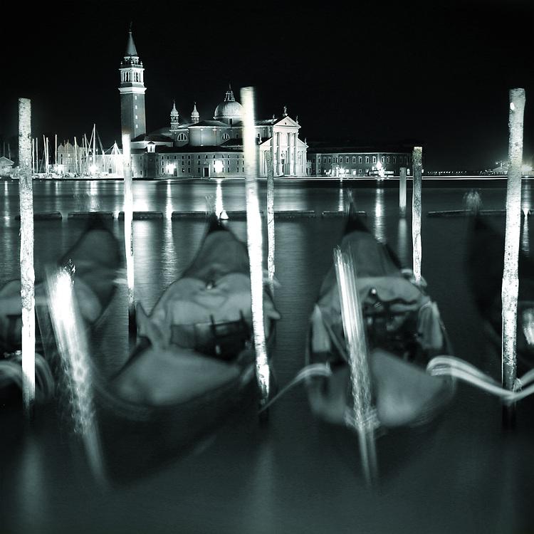 A night time shot of Gondolas with San Giorgio Maggiore in the background