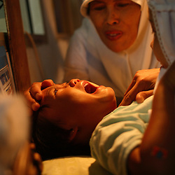 A young girl cries while being circumcised in Bandung, Indonesia on April 23, 2006. The families of 248 girls were given money to have their children circumcised in a mass circumcision celebration timed to honour the Prophet Mohammed's birthday. While religion was the main reason for circumcisions, it is believed by some locals that a girl who is not circumcised would have unclean genitals after she urinates which could lead to cervical cancer. It is also believed if one prays with unclean genitals their prayer won't be heard. The practitioners used scissors to cut the hood and tip of the clitoris. The World Health Organization has deemed the ritual unnecessary and condemns such practices.