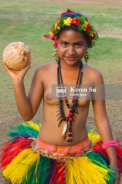 Yapese girl in traditional clothing carrying coconut at Yap Day Festival, Yap Island, Federated States of Micronesia