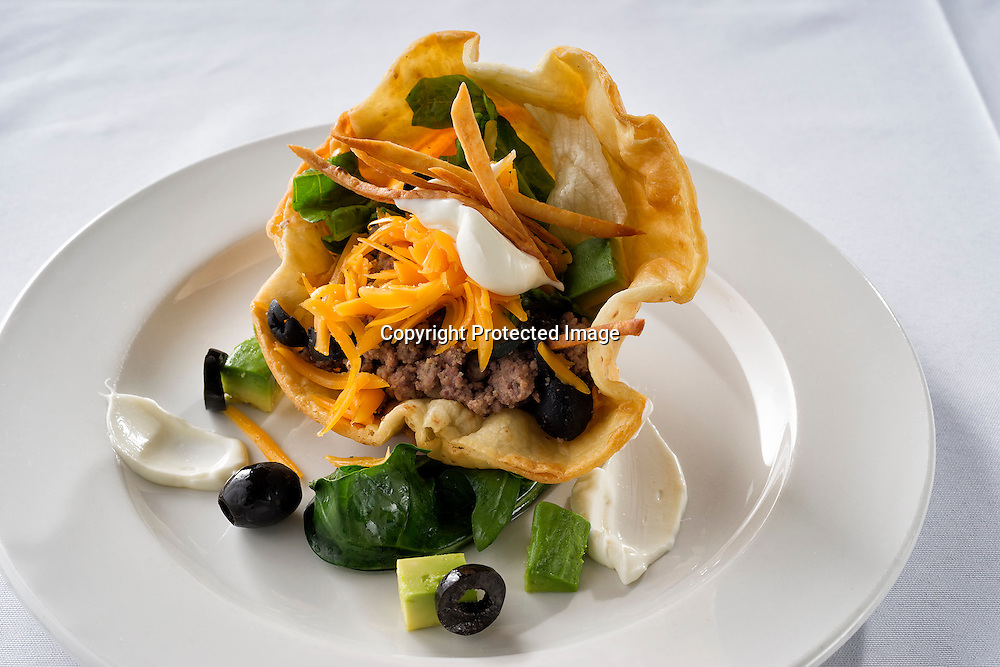 Taco salad on fried tortilla shell filled with hamburger meat, lettuce,sour cream,chedar cheese and black olives.
