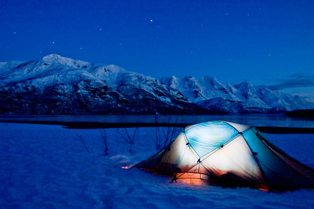 Campers light up a tent under a starry sky and big mountains.