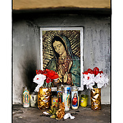 """SHOT 1/31/10 4:07:58 PM - A small and simple capilla near La Palma, Mexico along Highway 15. The Virgin of Guadalupe has symbolized the Mexican nation since Mexico's War of Independence. Our Lady of Guadalupe (Spanish: Nuestra Señora de Guadalupe) is a celebrated Catholic icon of the Virgin Mary also known as the Virgin of Guadalupe (Spanish: Virgen de Guadalupe). The Lady of Guadalupe is of significant importance to Mexican Catholics and has been given the titles of """"Queen of Mexico"""", """"Empress of the Americas"""", and """"Patroness of the Americas"""". Roadside capillas, or tiny chapels, in the Mexican states of Nayarit, Sinaloa and Sonora. The capillas are common along the roads and highways of Mexico which is heavily Catholic and are often dedicated to certain patron saints or to the memory of a loved one that has passed away. Often times they contain prayer candles, pictures, personal artifacts or notes. (Photo by Marc Piscotty / © 2010)"""