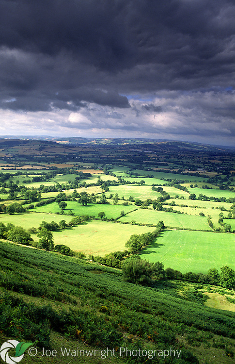 Rain clouds gather over the the rich pastures of the Onny Valley, viewed from the Long Mynd, Shropshire.
