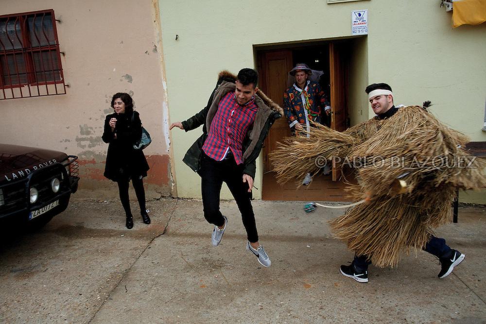 A man dressed as El Tafarron hits a reveller during El Tafarron festival on December 26, 2016 in Pozuelo de Tabara, Zamora province, Spain.  El tafarron is a pagan winter masquerade that takes place during Saint Esteban festivities. The festival is represented by El Tafarron and La Madama. El wears a custome of straw and a mask. (© Pablo Blazquez)