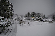 Fresh snow blankets family farms east of Oshu along the road into the high Kitakami Mountains.  Iwate Prefecture, Japan.