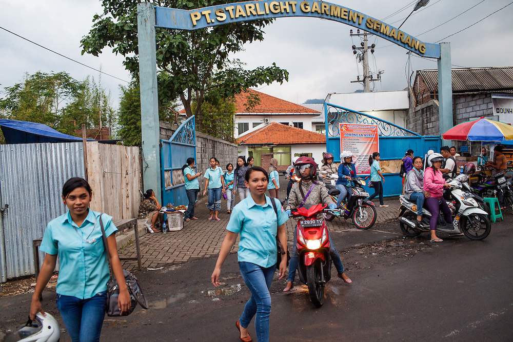 Garment workers of PT. Starlight Garment are seen leaving the factory a the end of their shift.  Taped on its front gate is a pink advertisement with various job positions that the factory has to offer.  Semarang, Indonesia.  May 14, 2013.