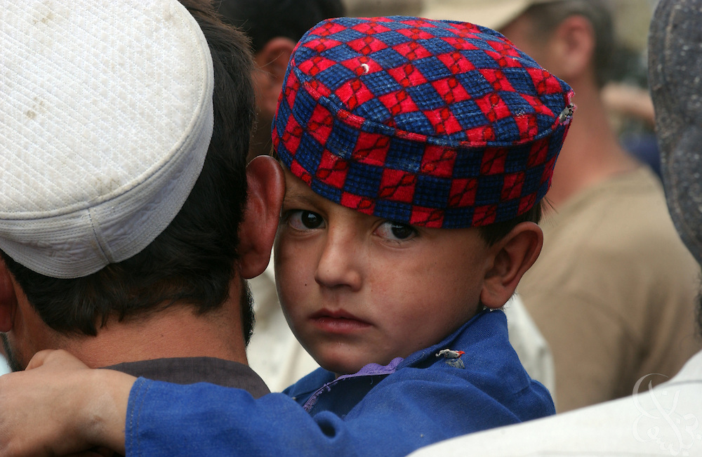 A young Afghan clings to his father as he waits for a medical checkup during a visit by British Royal Marines and U.S. Civil affairs to the boy's village June 18, 2002 in southeastern Afghanistan.