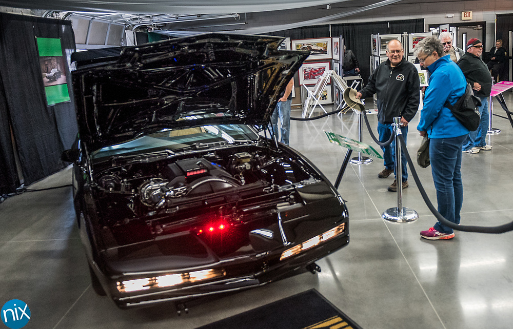 "Car enthusiast browse a display featuring KITT from the 1908s television show ""Knight Rider"" during the Charlotte AutoFair at Charlotte Motor Speedway Thursday morning."