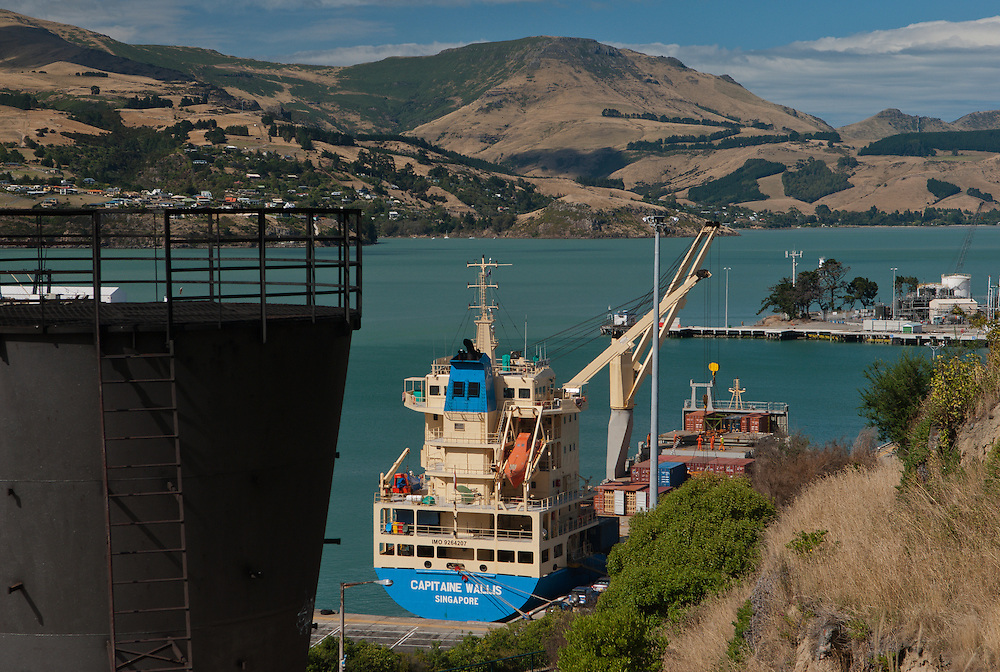 Container vessel Capitaine Wallis is docked in Lyttelton Harbour unloading cargo in view of the Banks Peninsula hills, with a tunnel vent in the foreground