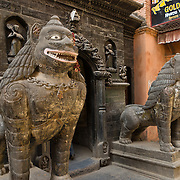 "Stone beasts guard the Golden Temple (Hiranya Varna, or Suwarna Mahavihara), which is a Buddhist Monastery existing since 1409 or earlier, located just north of Patan's Durbar Square, in Nepal, Asia. Patan was probably founded by King Veer Deva in 299 AD from a much older settlement. Patan, officially called Lalitpur, the oldest city in the Kathmandu Valley, is separated from Kathmandu and Bhaktapur by rivers. Patan (population 190,000 in 2006) is the fourth largest city of Nepal, after Kathmandu, Biratnagar and Pokhara. The Newar people, the earliest known natives of the Kathmandu Valley, call Patan by the name ""Yala""  (from King Yalamber) in their Nepal Bhasa language. UNESCO honored Patan's Durbar Square (Palace Square) as one of the seven monument zones of Kathmandu Valley on their World Heritage List in 1979. All sites are protected under Nepal's Monuments Preservation Act of 1956."