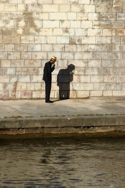 A man in a panama hat smokes a cigar while walking along the edge of the River Saône, in Lyon, France