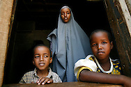 September 13, 2006 - Fartun Abdulah Adbrahman and two Somali children seek shelter from the sun while waiting with 320 Somali refugees at Liboi, Kenya near the border with Somalia before being transported to Dagahaley Refugee Camp in Dadaab. Somalis are fleeing from recent clashes between Islamic Courts and the Transitional Government of Somalia and the latest drought in the region. Over 21,000 refugees since January 2006 have arrived in Dadaab, in the North Eastern province of Kenya. Despite the recent influx of refugees, funding by the international community has been reduced, according to CARE International. (Photo by Jakub Mosur/Polaris)