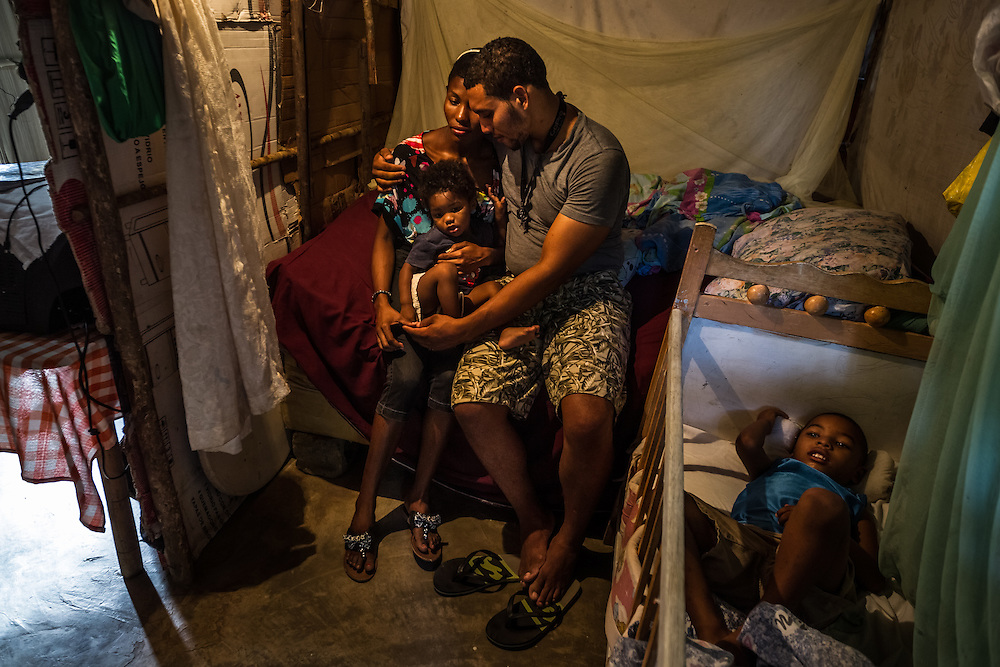 """SABANETA DE YÁSICA - JUNE 28, 2015: Robert Rosario Almonte, 24, a Dominican, and his wife Yoselin Bernard, 24, who was born in the Domincan Republic to Haitian parents with a midwife at their home, pose for a portrait with their two children, Daniel Angel Rosario Bernard, 3, and Dariel Rosario Bernard, 1, at their humble home, built of tree branches, sheetmetal and cardboard, in the La Catalina neigborhood. Yoselin and their children are unable to get identification papers because she never got a birth certificate since she was not born in a hospital.  If the police find her, they will legally be able to deport her and their children to Haiti under law 169-14. She is very frightened and rarely leaves their home. She said she does not know which country she belongs to, because neither Haiti nor The Dominican Republic will give her documents. She said she feels like she doesn't have a country, that she is just up in the air"""". PHOTO: Meridith Kohut for The New York Times"""