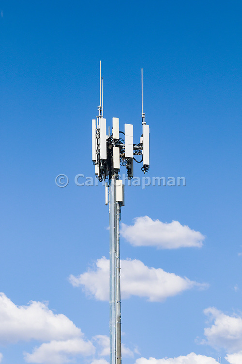 3 sector cellular telecom communications panel antenna array for the mobile telephone system on a cellsite pole tower against cumulus clouds.