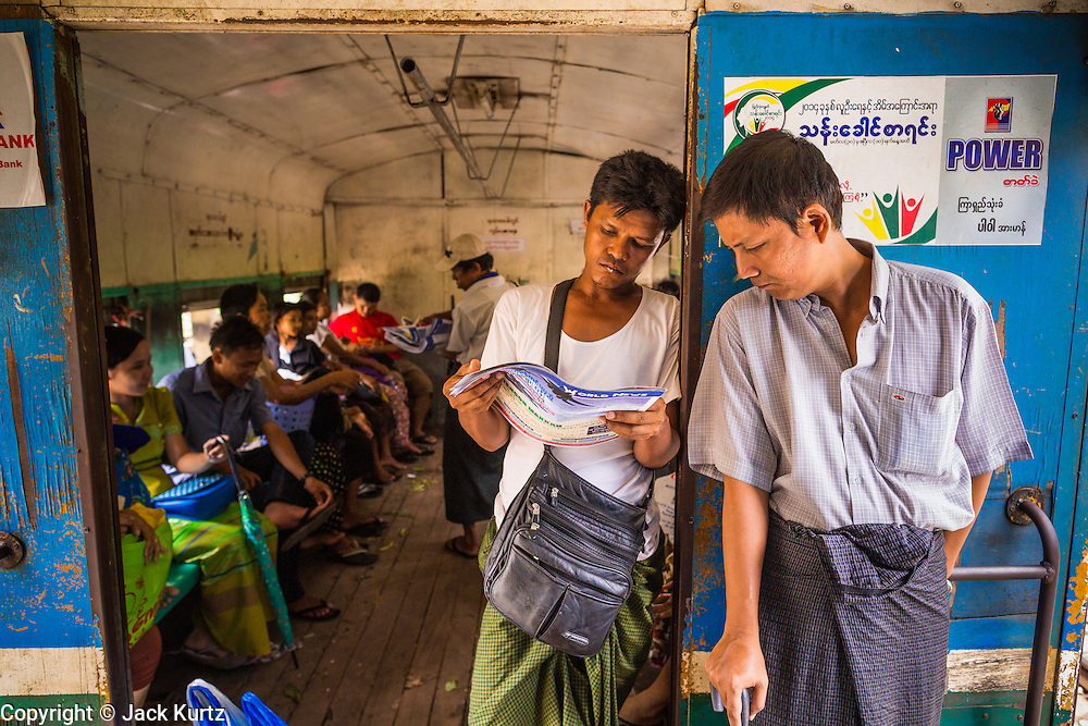05 JUNE 2014 - YANGON, YANGON REGION, MYANMAR: Men read a newspaper on the Yangon Circular Train. The Yangon Circular Train is a commuter train that circles Yangon, Myanmar (Rangoon, Burma). The train is 45 kilometers long, makes 38 stops and takes about three hours to make a loop of the city.     PHOTO BY JACK KURTZ