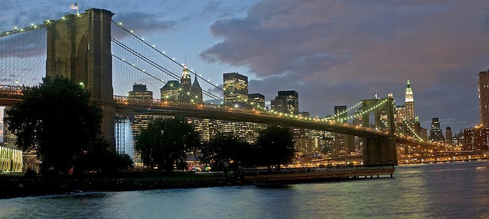 Brooklyn Bridge; New York City, NY, designed by John Augustus Roebling, waterfall designed created by Olafur Eliasson, Manhattan, Dusk