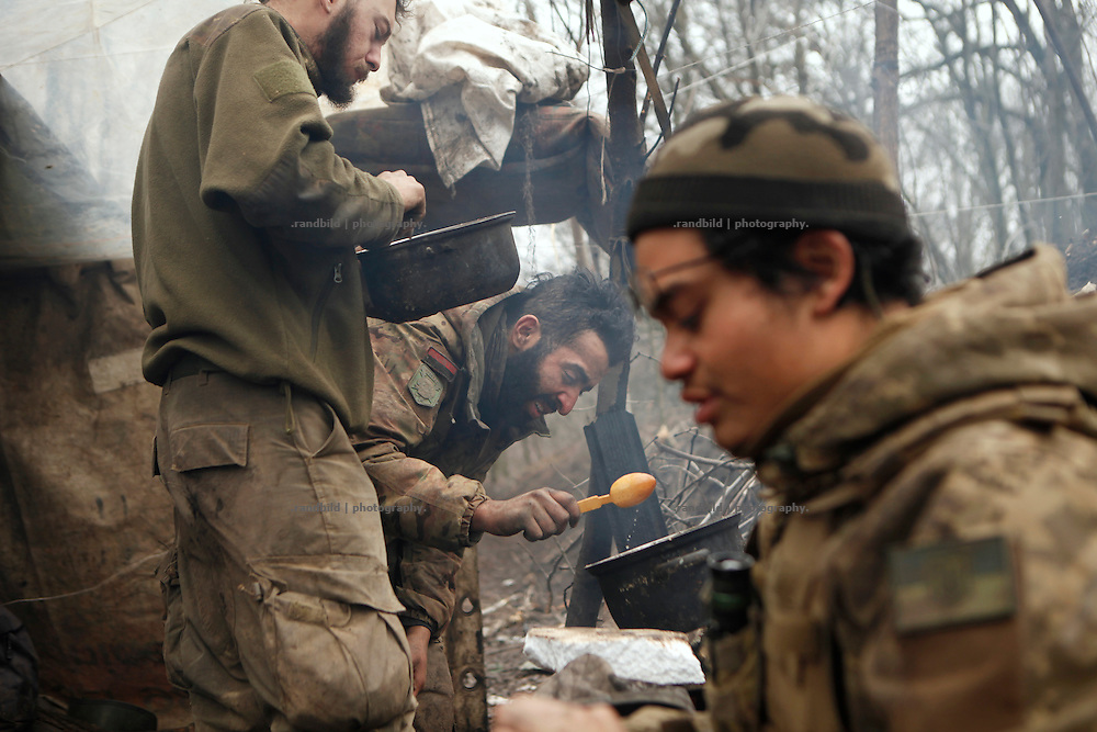 While Charlie (ri.) cleans his Kalashnikov, Ben (ce.) and Alex (le.) prepare a meal at the camp fire.<br />
