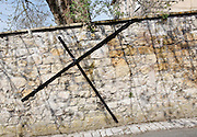 Steel reinforcing cross on bowing limestone wall by the path of the Cotswold Way Sion Hill, Bath