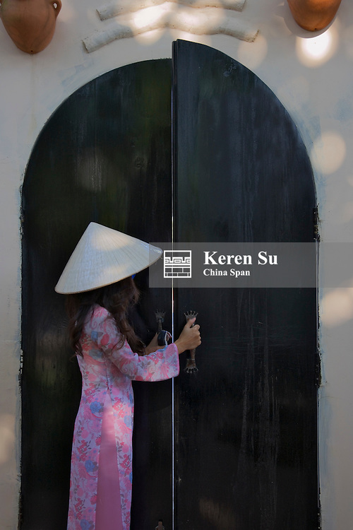 Girl with conical hat by traditional door.