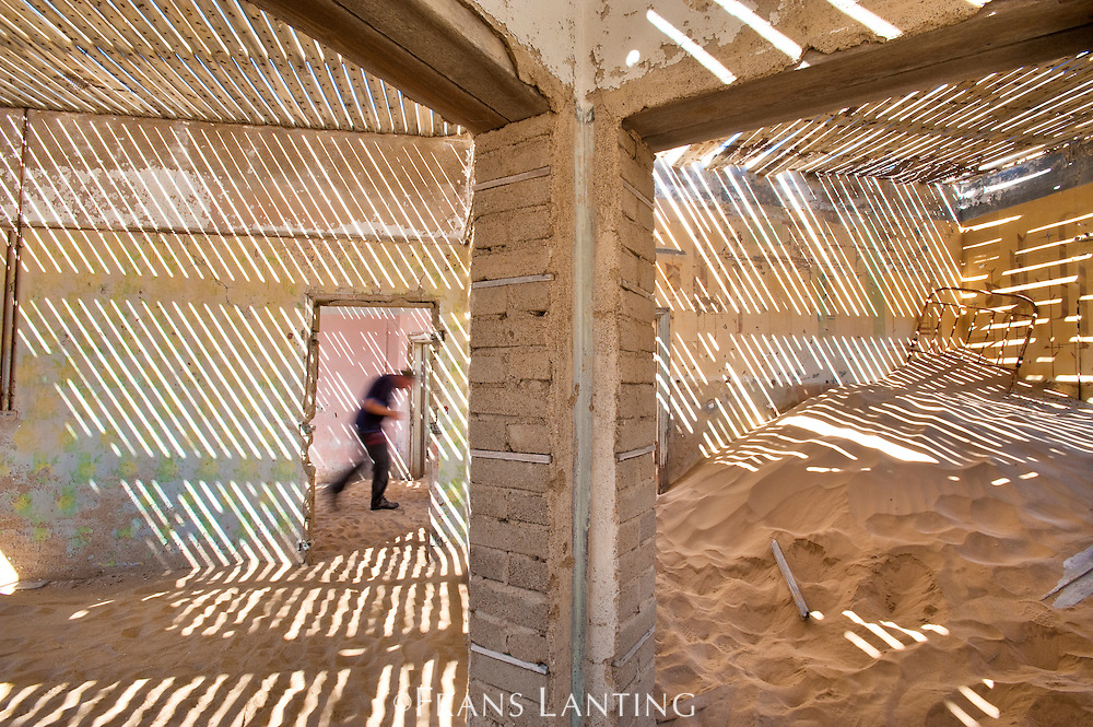Tourist walking through ghost town building filled with sand, Kolmanskop, Sperrgebiet National Park, Namibia