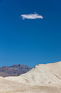 A single cloud floats above land formations in Death Valley National Park, California