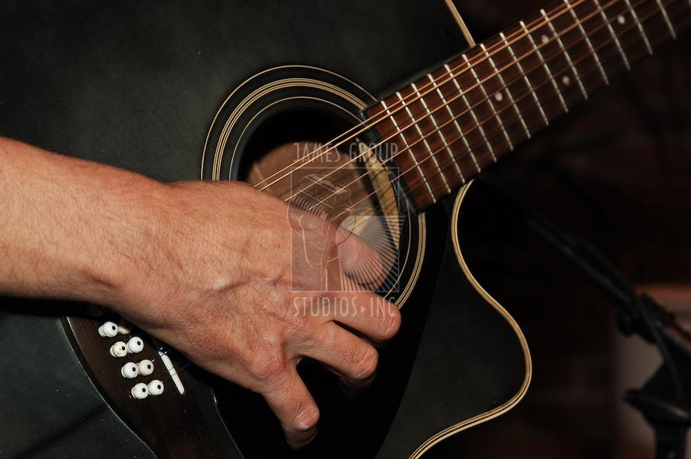 closeup of guitarist's hands strumming a guitar