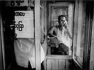 Man pays to talk in a private telephone box, Burmese, Yangon, Burma.