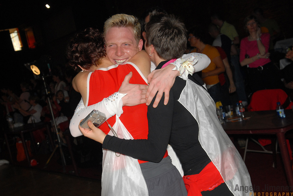 Pascal Herrbach, center, of Berlin, Germany,  hugs fellow dancers after winning the championship in the men's latin A division of the same-sex ballroom dancing competition during the 2007 Eurogames at the Waagnatie hangar in Antwerp, Belgium on July 13, 2007. ..Over 3,000 LGBT athletes competed in 11 sports, including same-sex dance, during the 11th annual European gay sporting event. Same-sex ballroom is a growing sports that has been happening in Europe for over two decades.