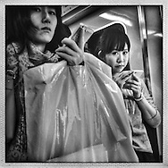 Now, we are watching each other.  Two young women holding smart phone with high-definition video capabilities to record the world around them at will, including criminal activity.  Tokyo, Japan.