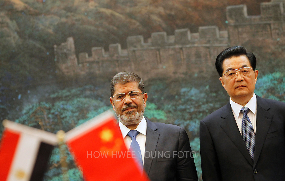 epa03372193 Egypt's President Mohamed Morsi (C) and his Chinese counterpart Hu Jintao (R) attend a signing ceremony in the Great Hall of the People in Beijing, China, 28 August 2012. Second left is Egyptian Foreign Minister Mohammed Kamel Amr. Morsi is in China on a three-day visit after which he will stop off in Tehran for a Summit of the Non-Aligned Movement on 30 August.  EPA/HOW HWEE YOUNG