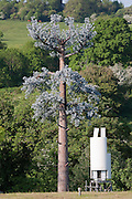 "False Tree Mobile Phone Mast / Fake Cell phone Antenna Tower and white transmitter in English landscape..Disguised ""Antenna Tower in the form of a Tree""  at the Offices of AlanDick  located next to the A40 at Charlton Kings. Cheltenham, Gloucestershire, England"