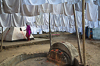 Hotel linens hang to dry among Hindu shrines in Dhobi Chour, the section of Kathmandu that is home to the caste of washers and others who work in the laundry industry.